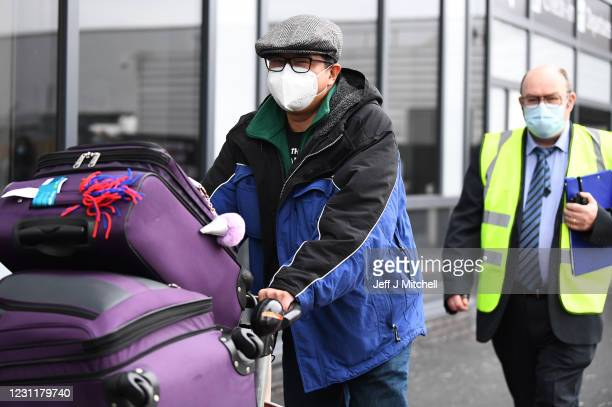 Passenger arriving at Edinburgh Airport from the United States via Dublin is escorted towards transport to a quarantine hotel on February 15, 2021 in...