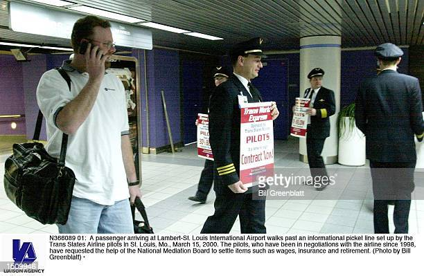A passenger arriving at LambertSt Louis International Airport walks past an informational picket line set up by the Trans States Airline pilots in St...