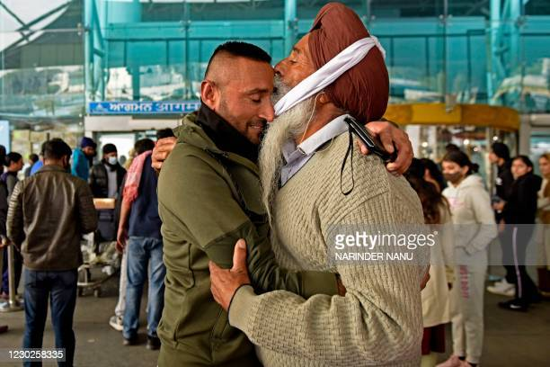 Passenger arriving from the United Kingdom receives a hug by his father after he went through a Covid-19 coronavirus test at Sri Guru Ram Dass Jee...