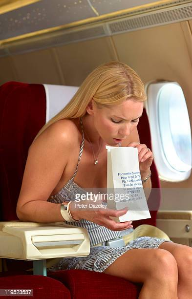 passenger being sick on plane - sick bag stock photos and pictures