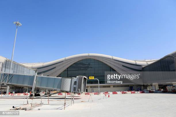 A passenger boarding bridge sits above an aircraft parking bay on the runway site at Abu Dhabi airport's MidField terminal during construction in Abu...