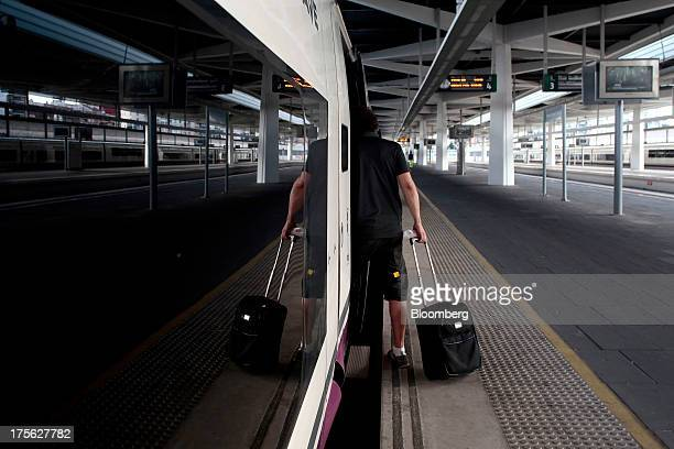 A passenger boards an Alta Velocidad Espanola highspeed train operated by Renfe Operadora SC at Joaquin Sorolla railway station in Valencia Spain on...