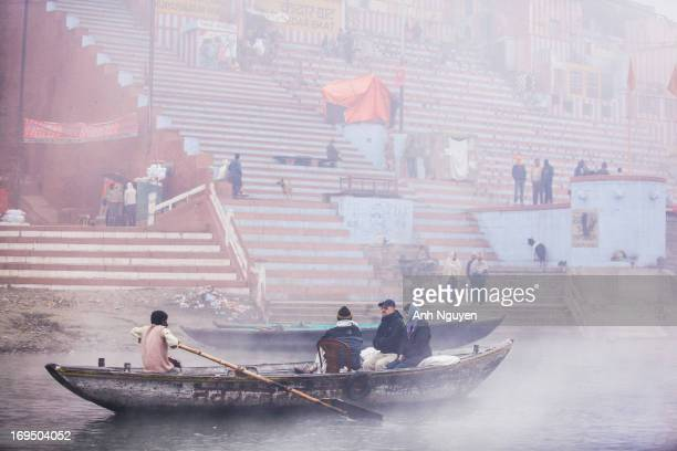 Passenger boat on a cruise trip along the Ganges river in a misty early winter morning along the riverside of Old City of Varanasi, the most sacred...