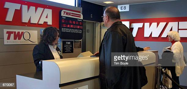 A passenger bound for St Louis MO checks in at the Trans World Airlines gate for a ticket agent January 8 2001 at Chicago's O''Hare International...