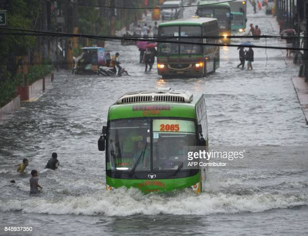 A passenger bus manoeuver along a flooded main street in Manila on September 12 after tropical depression locally codenamed 'Maring' hit the eastern...