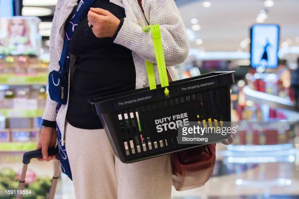 A passenger carries goods in a duty free storebranded shopping basket of Lisbon International airport operated by ANAAeroportos de Portugal SA in...