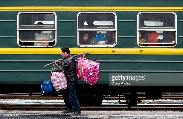 A passenger carries his belongings to a boarding train at the Wenzhou Railway Station on January 23 2011 in Wenzhou of the Zhejiang Province China...