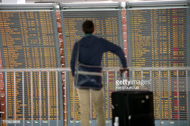 A passenger checks a board which shows departing flights many of which are cancelled on June 11 2013 at Roissy Charles de Gaulle international...