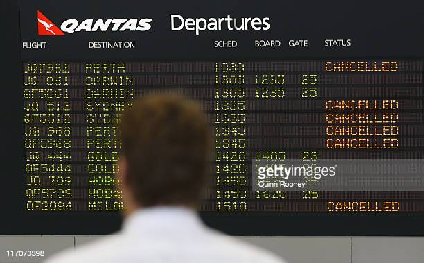 A passenger checks a departure screen as airlines cancel flights due to volcanic ash at Melbourne Domestic Airport on June 21 2011 in Melbourne...