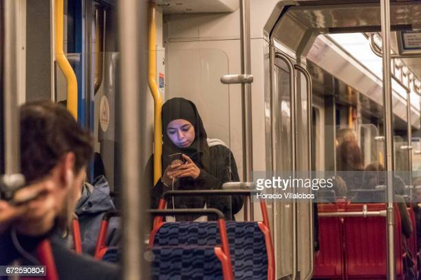 A passenger checks her cellphone while riding the Metro on April 20 2017 in Amsterdam Netherlands The city's Metro system was first introduced in...