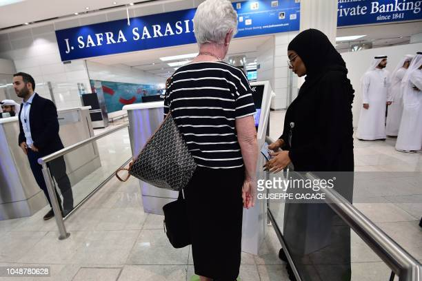 A passenger checks her passport at an Egate an automated border control selfservice at Dubai International Airport's terminal 3 in the United Arab...