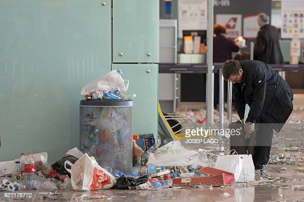 A passenger checks his bag in a hall of BarcelonaEl prat aiport littered with pieces of paper and rubbish during a strike of the airport cleaning...