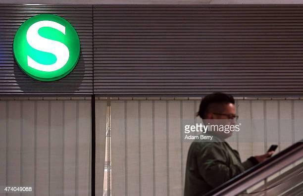 A passenger checks his mobile phone as he rides an escalator past the SBahn regional train logo at Friedrichstrasse station during a train strike on...