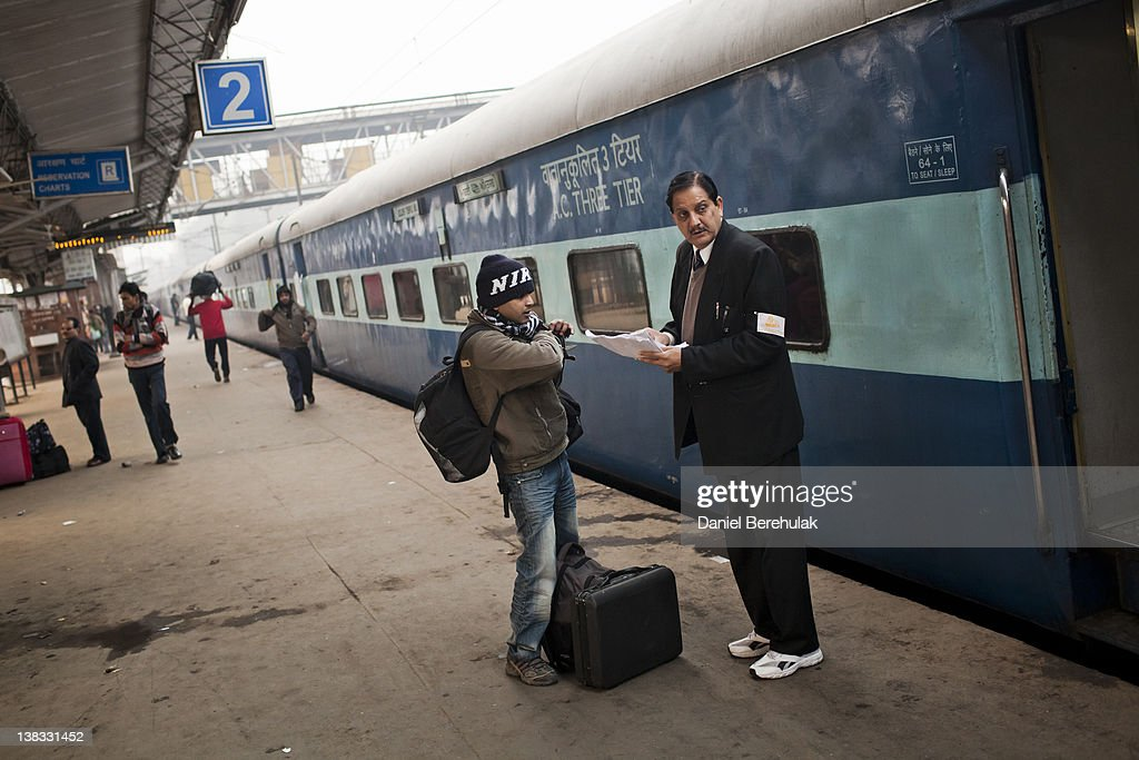 A passenger checks his seating on the Amritsar bound train as he receives help from a conductor at the Nizamuddin Railway Station on February 06 2012.