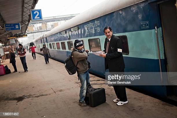 A passenger checks his seating on the Amritsar bound train as he receives help from a conductor at the Nizamuddin Railway Station on February 06 2012...