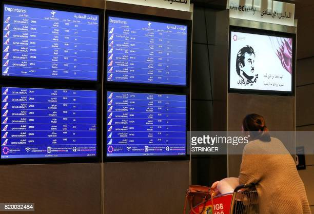 A passenger checks the departures board at the Hamad International Airport in Doha on July 20 2017