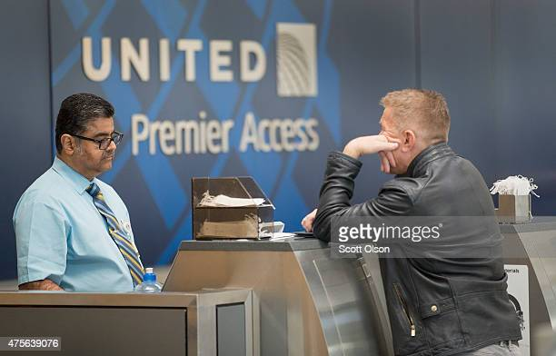 A passenger checksin for a flight with United Airlines at O'Hare Airport on June 2 2015 in Chicago Illinois United travelers experienced widespread...