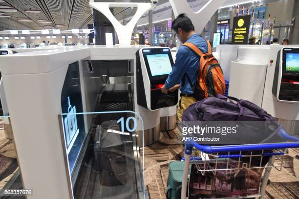 A passenger checksin his luggage using an automated booth at the newlyopened Changi International Airport's Terminal 4 in Singapore on October 31...