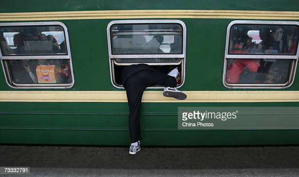 A passenger climbs into a train through the window Nanjing Railway Station during the Chunyun peak travel period on February 15 2007 in Nanjing of...