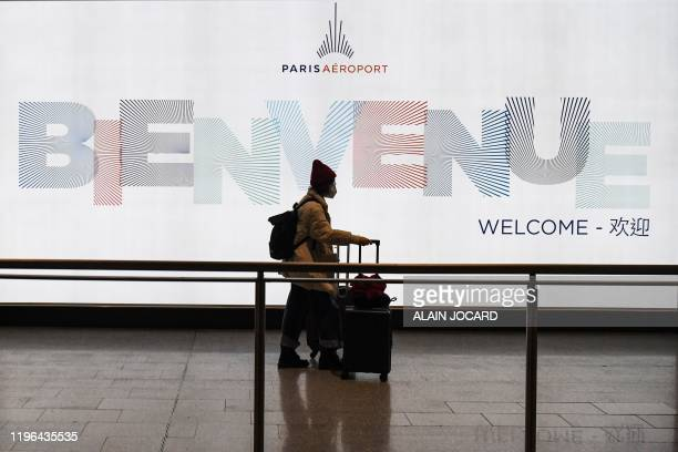 Passenger coming from China, leaves the Terminal wearing a protective face mask after landing in Charles De Gaule Airport on January 26, 2020 in...
