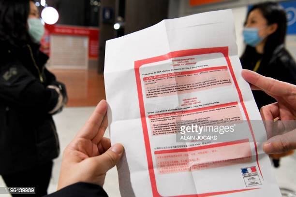 Passenger coming from China reads a medical survey at the arrival Terminal in Charles De Gaulle Airport on January 26, 2020 in Roissy-en-France. -...