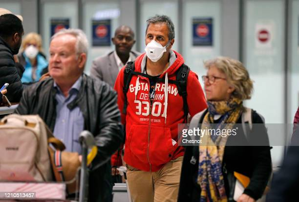 Passenger coming from China wearing a protective mask leaves the terminal 2 after landing at Roissy Charles de Gaulle airport on March 5, 2020 in...