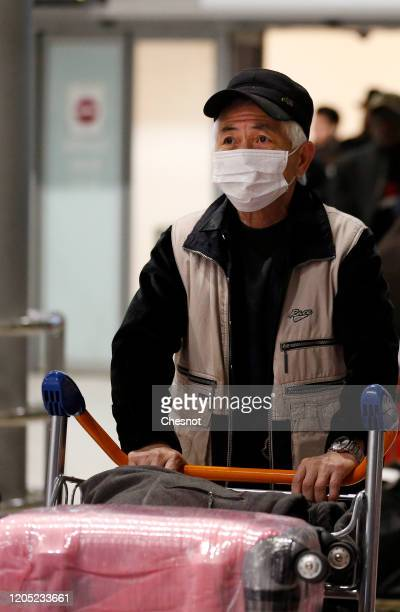 Passenger coming from China wearing a protective mask leaves the Terminal after landing in Charles De Gaulle Airport on February 10, 2020 in...