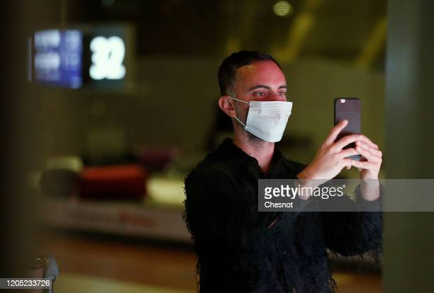 Passenger coming from China, wearing a protective mask uses his cellphone as he leaves the Terminal after landing in Charles De Gaulle Airport on...