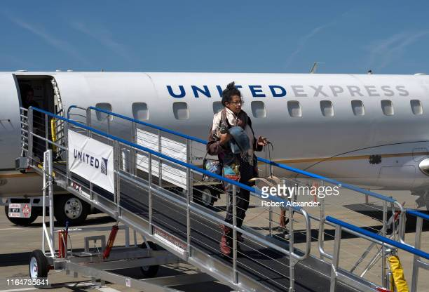 A passenger disembarks a United Express passenger plane after landing at Medford International Airport in Medford Oregon