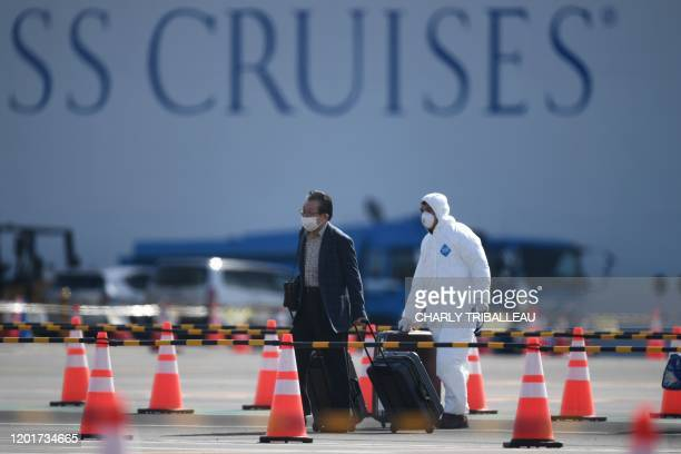 TOPSHOT A passenger disembarks from the Diamond Princess cruise ship in quarantine due to fears of the new COVID19 coronavirus at the Daikoku Pier...