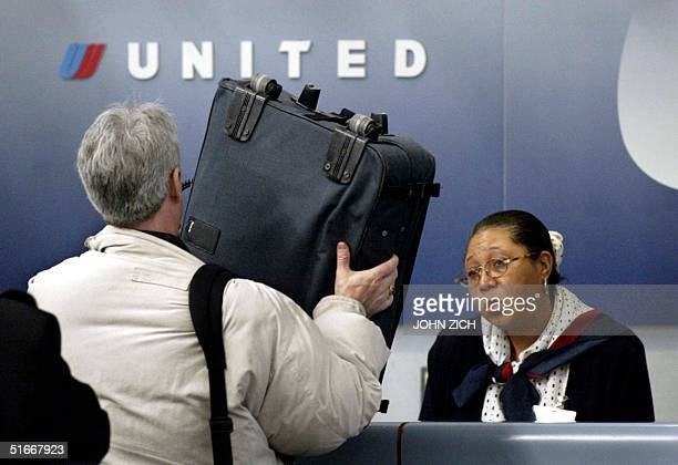 A passenger displays his carryon bag to a United ticket agent 05 December 2002 at O'Hare International Airport in Chicago Illinois UAL's request for...