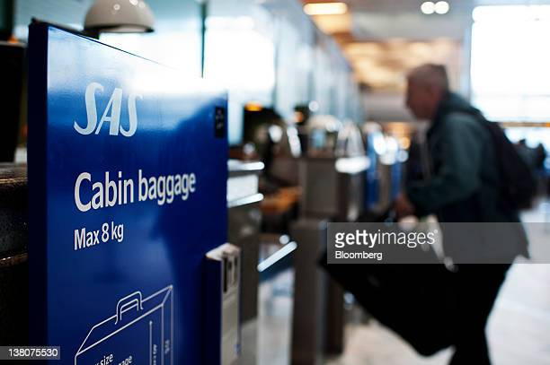 A passenger drops off his luggage at the SAS AB baggage desk at Landvetter airport near Gothenburg Sweden on Wednesday Feb 1 2012 SAS partowned by...