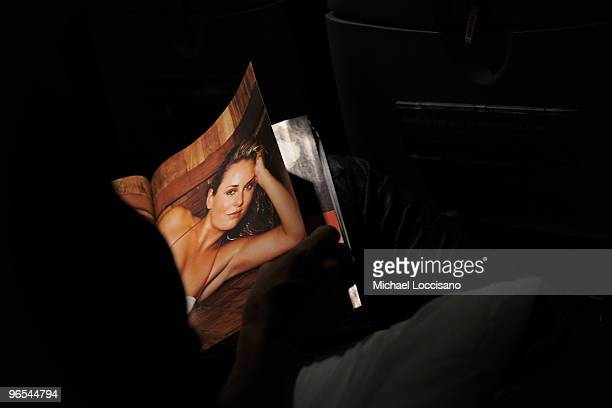 A passenger eyes a spread of skiier Lindsey Vonn while browsing the pages of the Sports Illustrated 2010 swimsuit issue on board the Sports...