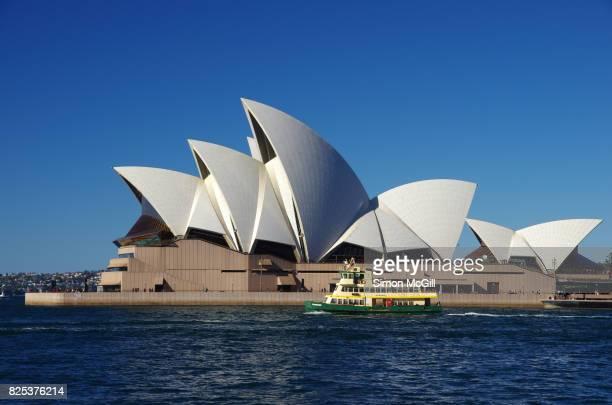 a passenger ferry passes the sydney opera house, bennelong point, sydney, new south wales, australia - パフォーミングアートセンター ストックフォトと画像