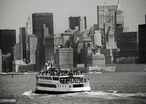 A passenger ferry sails through New York Harbour offering panoramic views of the Lower Manhattan skyline with the Twin Towers seen in the distance