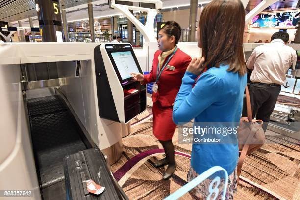 A passenger gets help from staff to checkin her luggage on an automated booth at the newlyopened Changi International Airport's Terminal 4 in...