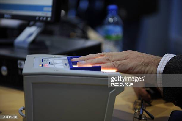 A passenger gets his fingers scanned by an agent of the French customs police on October 19 2009 at RoissyCharles de Gaulle international airport...