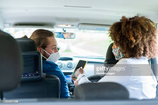 passenger giving directions to a mobile application driver to reach their destination - world sports championship stock pictures, royalty-free photos & images