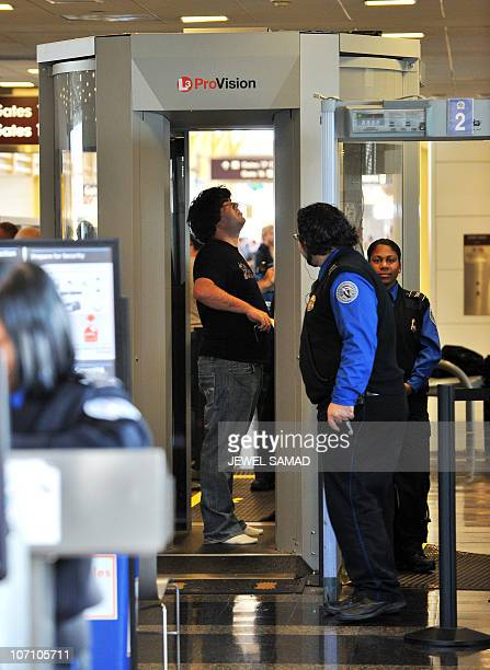 A passenger goes through a full body scanner at Reagan National Airport in Washington DC on November 24 2010 ahead of Thanksgiving Day US airline...