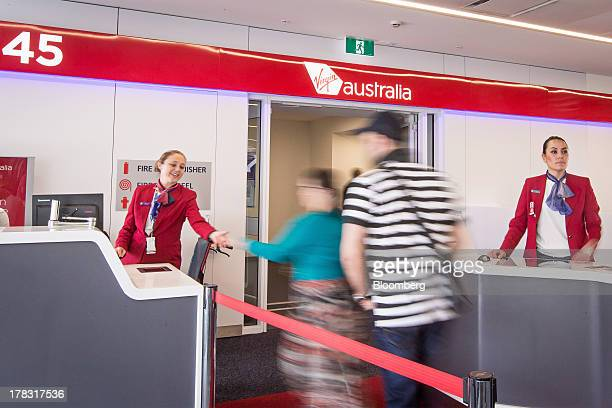 A passenger hands over her boarding pass to a Virgin Australia Holdings Ltd employee at a departure gate in the domestic terminal of Sydney Airport...