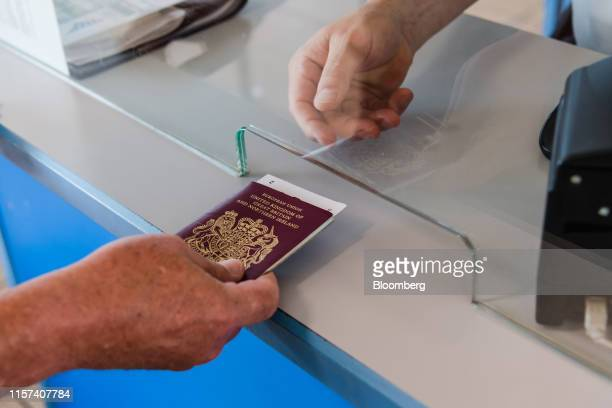 A passenger hands over their UK passport for inspection at a border control kiosk in the PO Ferries Ltd terminal at the Port of Zeebrugge in...