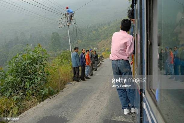 A passenger hangs from a door as locals watch the Toy Train pass by on its way to Darjeeling through the Himalayan foothills The Darjeeling Himalayan...