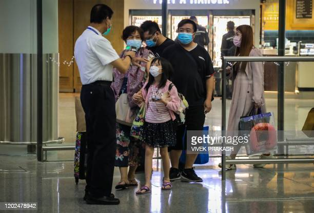 A passenger has her temperature measured by airport health staff with an infrared thermometer after arriving inside Hong Kong International Airport...