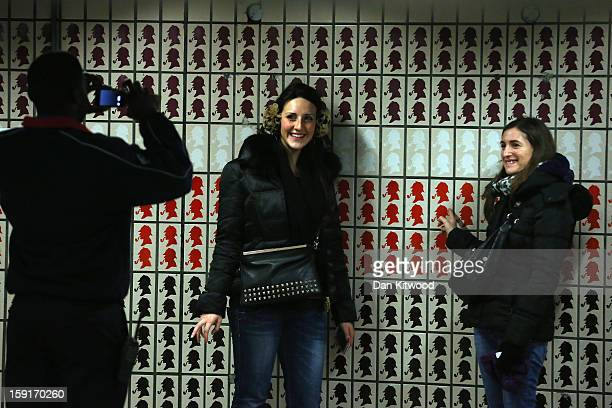 Passenger have their pictures taken in front of Sherlock Holmes themed tiles at Baker Street Underground Station on January 9 2013 in London England...