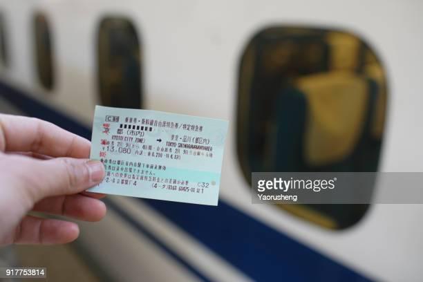 Passenger hold a Shinkansen Train ticket travel from Kyoto to Tokyo,Japan.