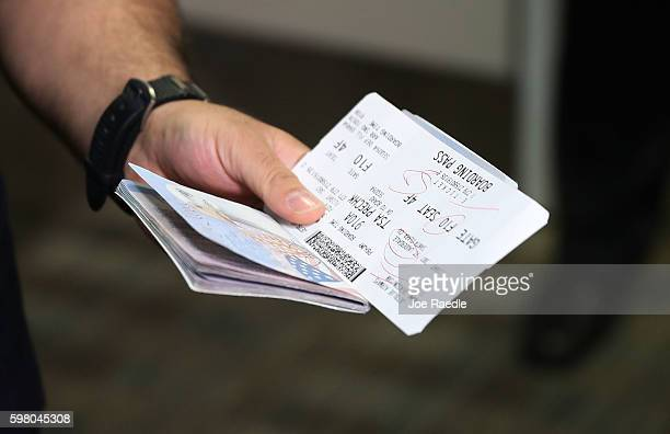 A passenger holds his passport and ticket at the Fort LauderdaleHollywood International Airport as he checks in for JetBlue Flight 387 the first...