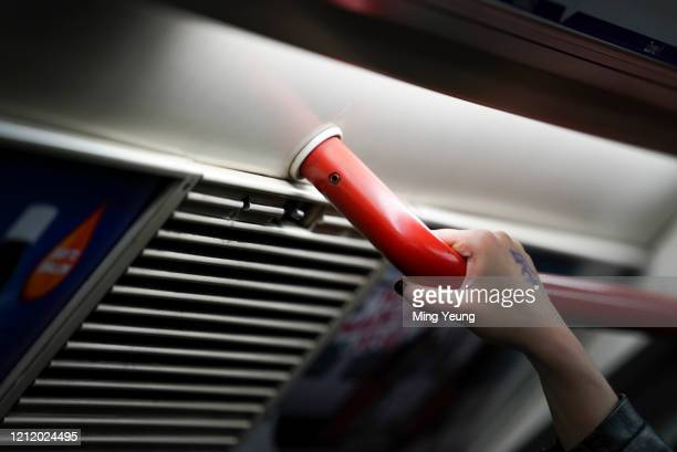 Passenger holds the handrail on the London Underground as governments ask people to wash their hands during the Coronavirus pandemic in London on...