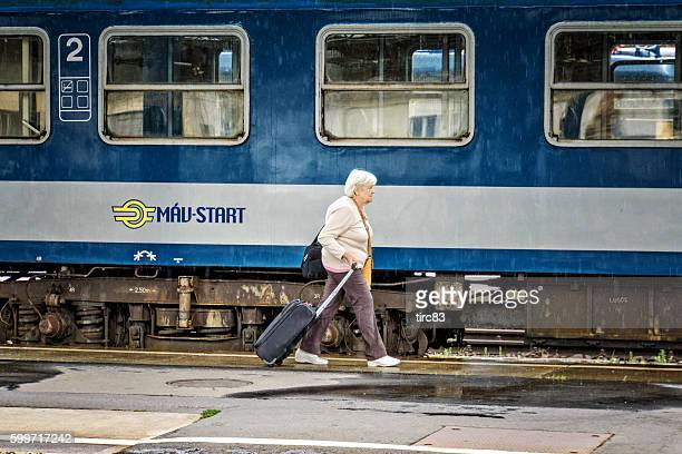 Passenger hurrying for train. Woman pulling her suitcase on platform