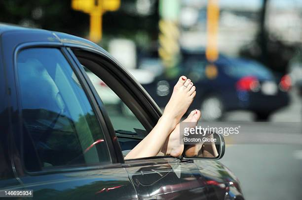 A passenger in a car near the Museum of Science in Cambridge enjoys the warm temperatures on Friday June 15 2012 as she rides with her bare feet out...
