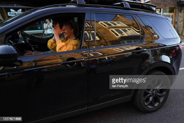 A passenger in a car reacts as they drive past residents of homes and flats in Saltburn who come out to applaud NHS staff and key workers on May 28...